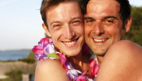 Two men embracing outdoors, one wearing lei