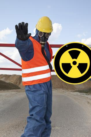Germany, Man in protective workwear near radioactive warning symbol