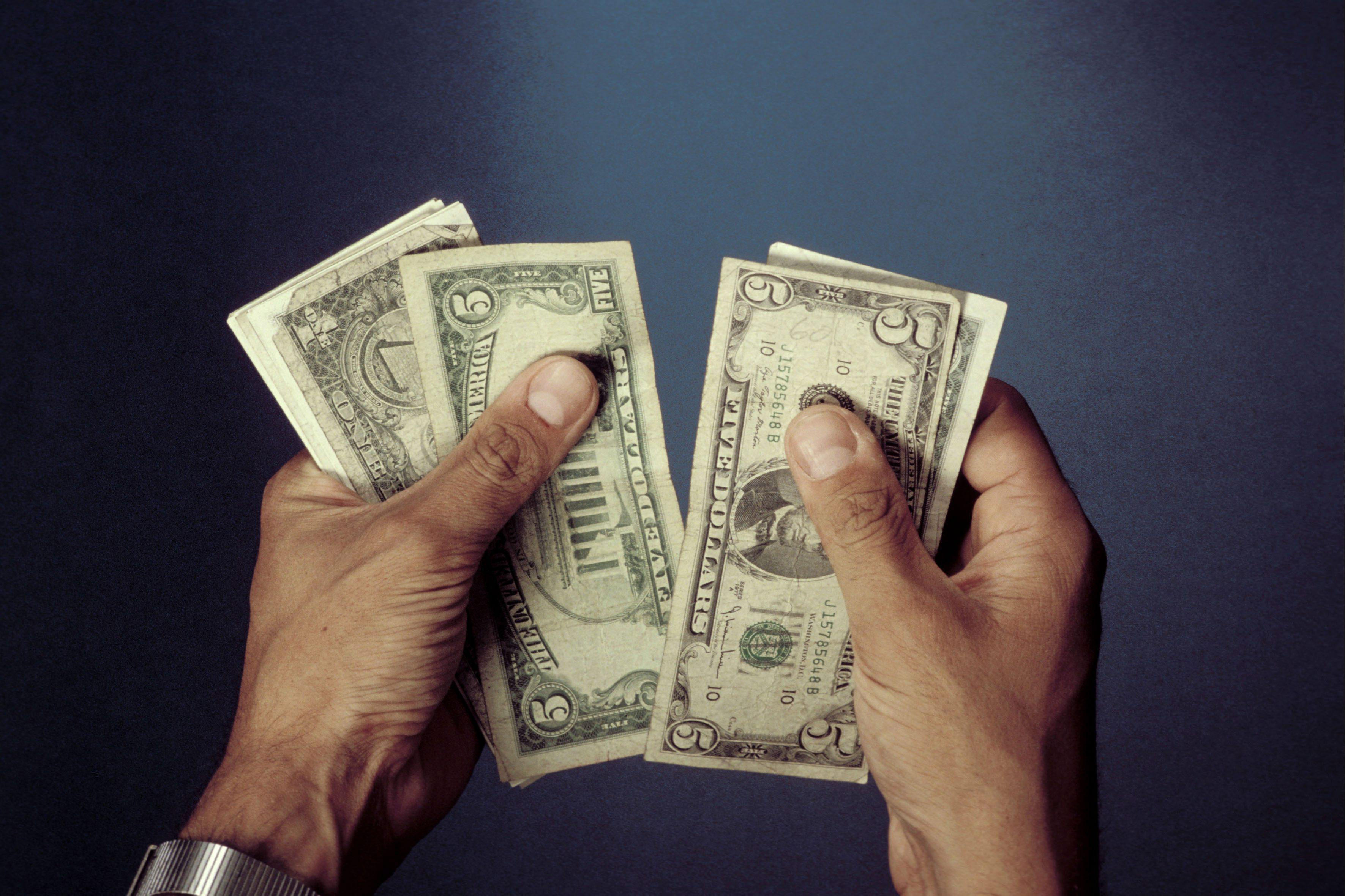 Hands with US - Dollars.
