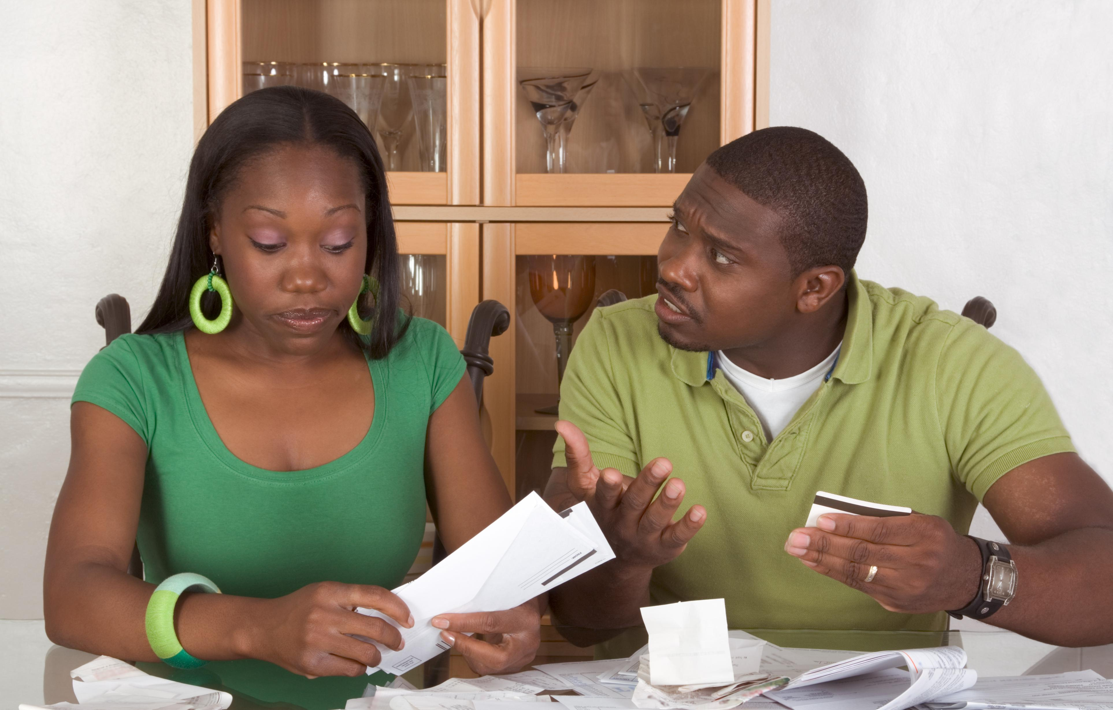 Young black African American couple sitting by glass table and trying to work through pile of bills, frustrated by amount of expenses during economic crises recession times hoping for stimulus plan to work or expecting bailout money