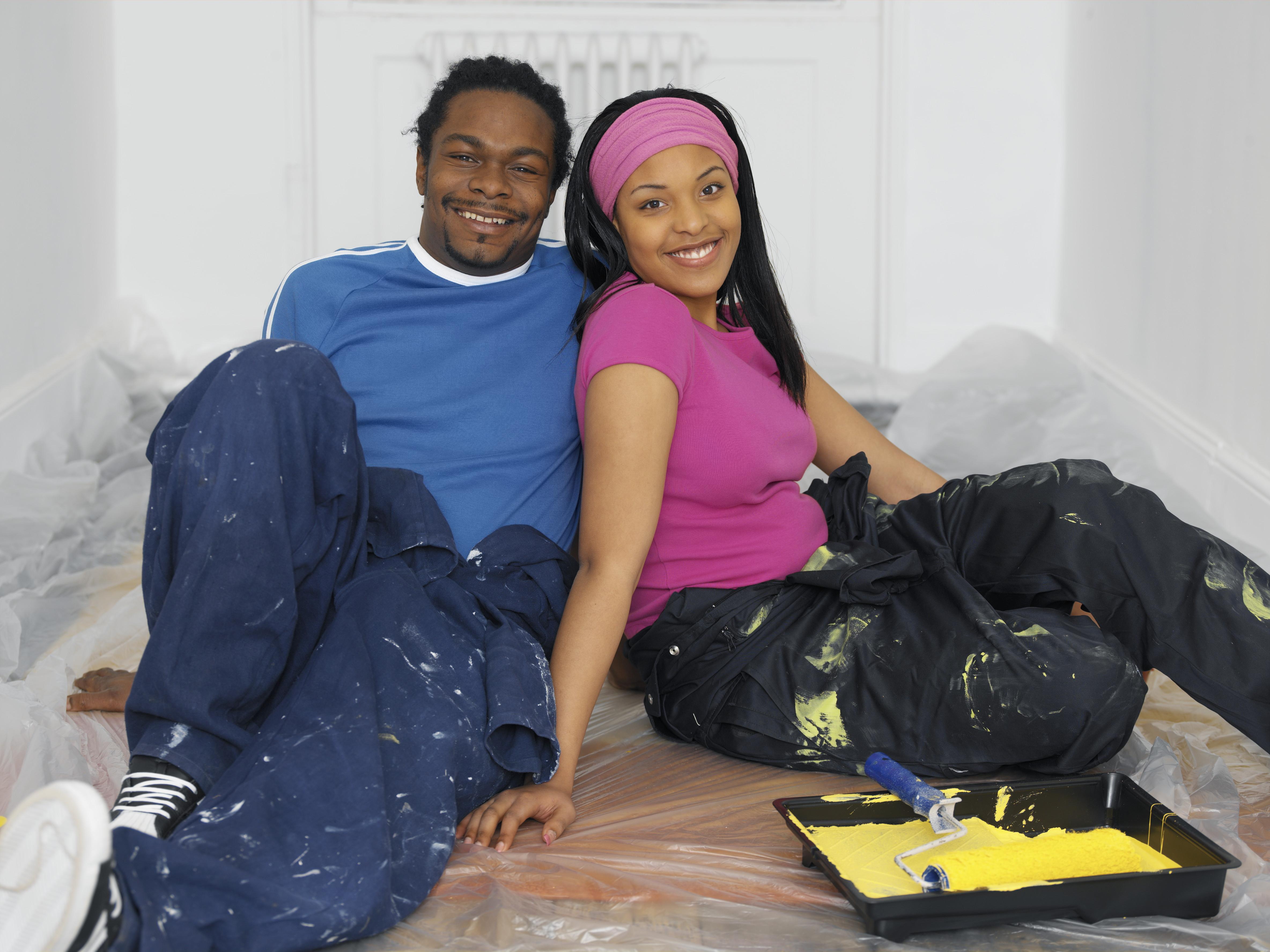 Young man and woman sitting on floor in decorating overalls, smiling