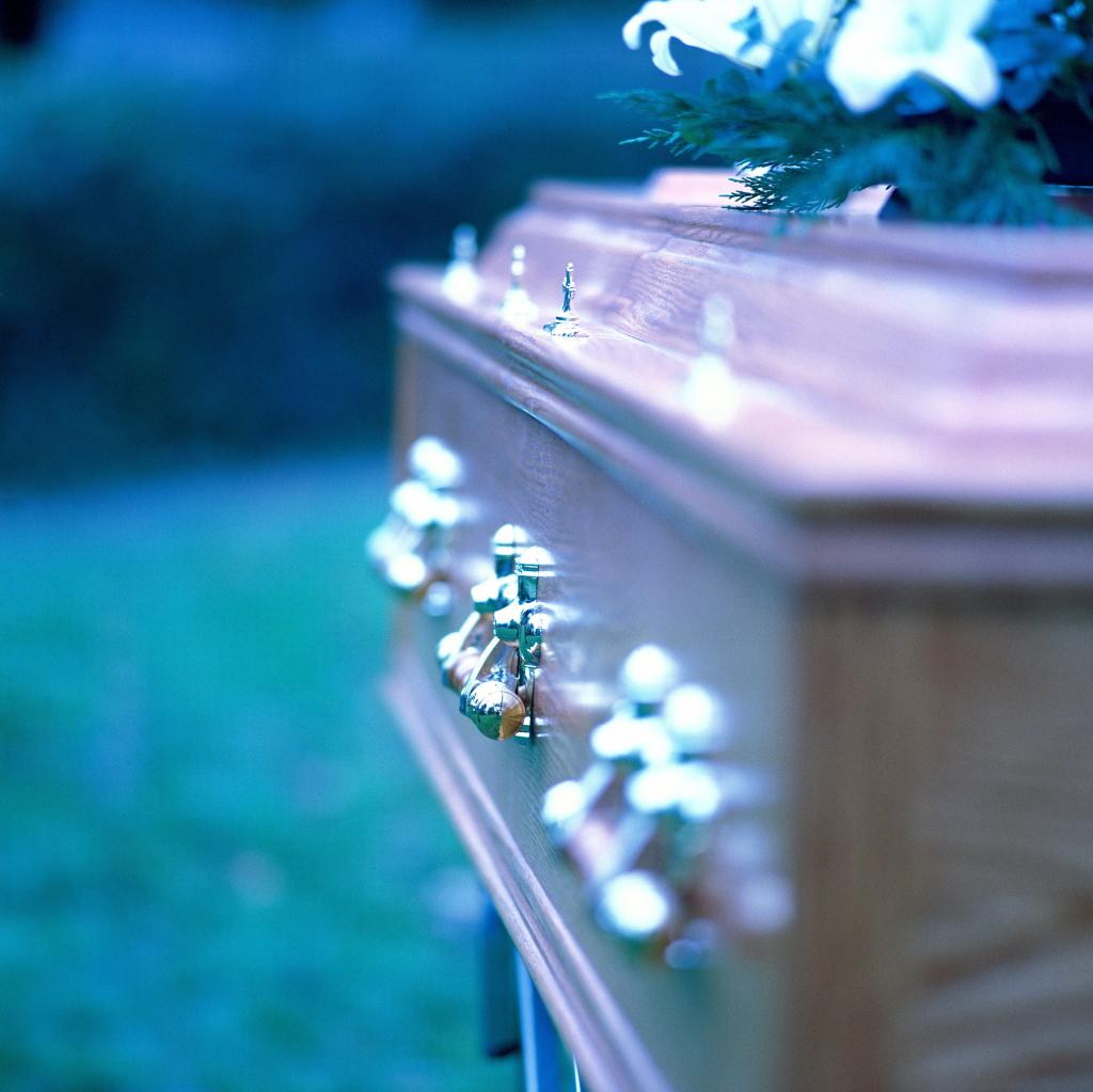 close-up of the side of a coffin with brass handles