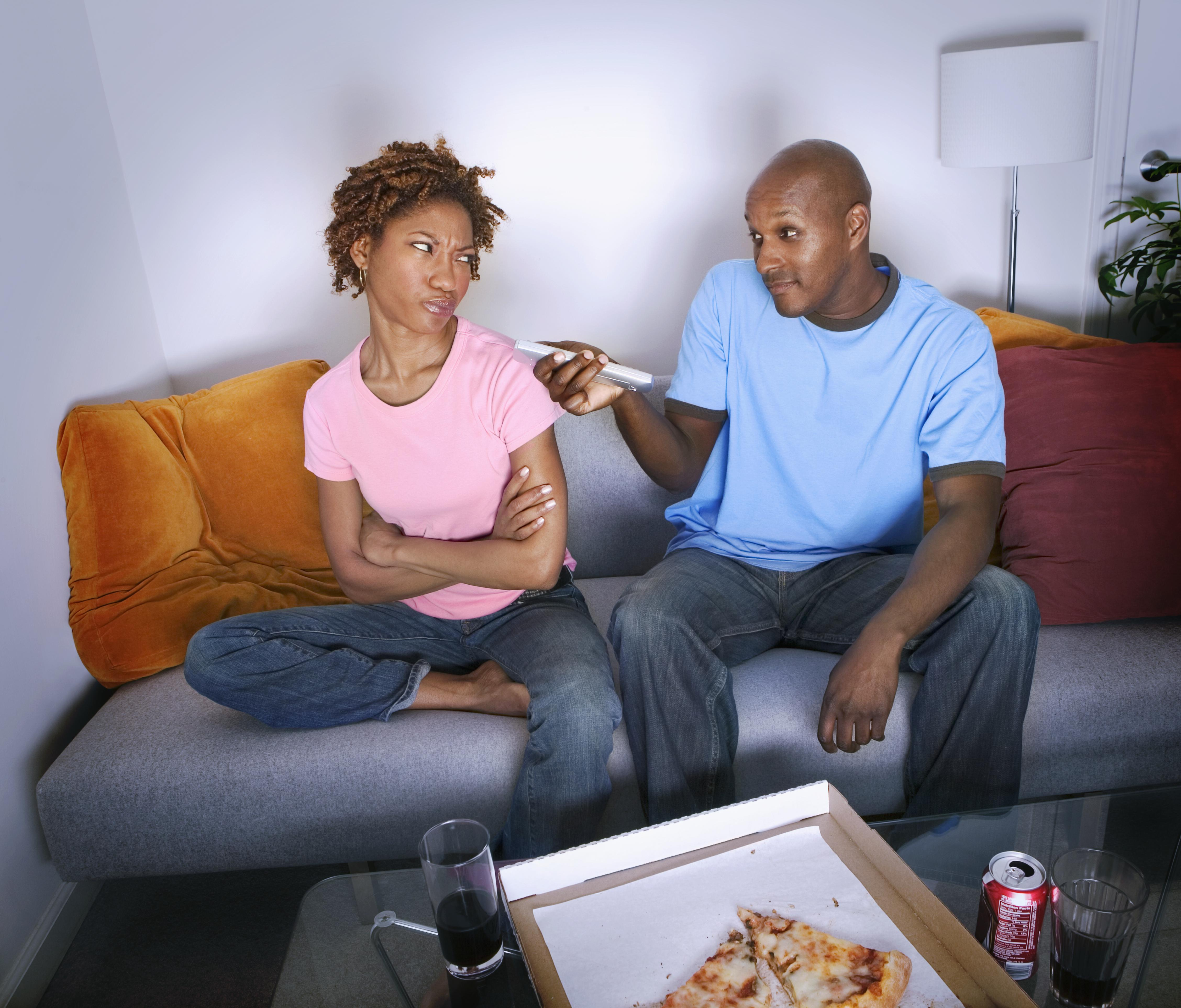 African man pointing remote control at annoyed girlfriend