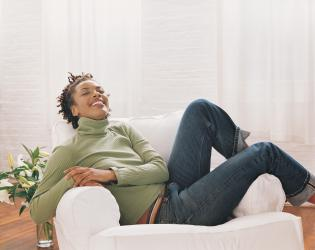 Portrait of a Woman Lying on an Armchair in a Living Room