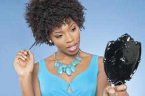Attractive African American woman looking at herself in mirror over colored background