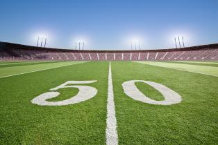 50 yard line on football field in stadium.