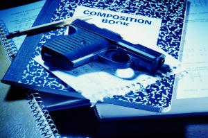 Handgun on school books, close-up
