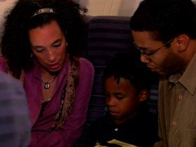 A mother and father read a book to their son while seated on an airplane.