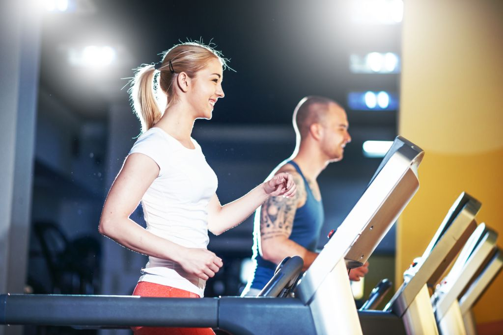 Two caucasian athletes warming up on treadmill in gym