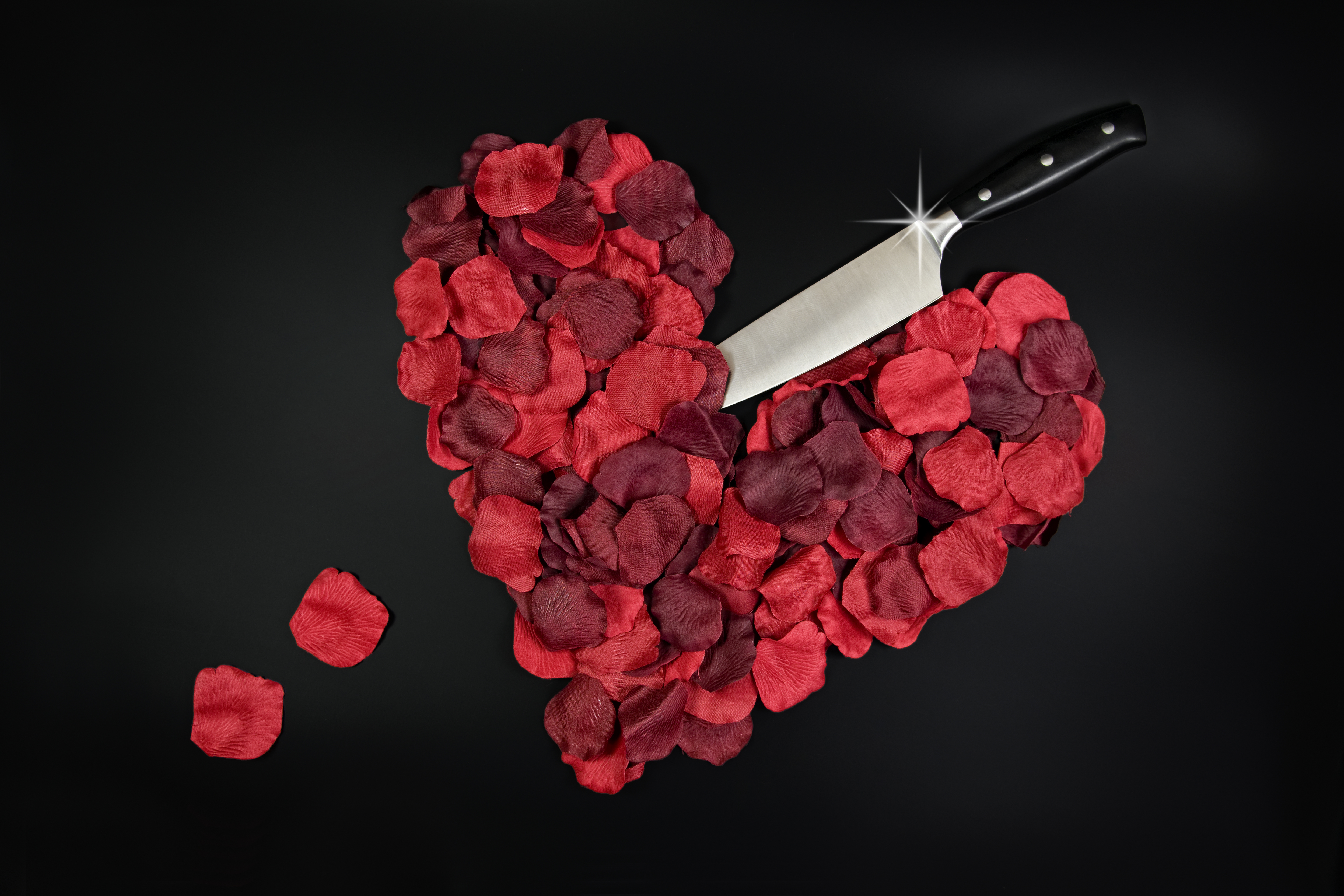 Red rose petals in heart shape with large knife