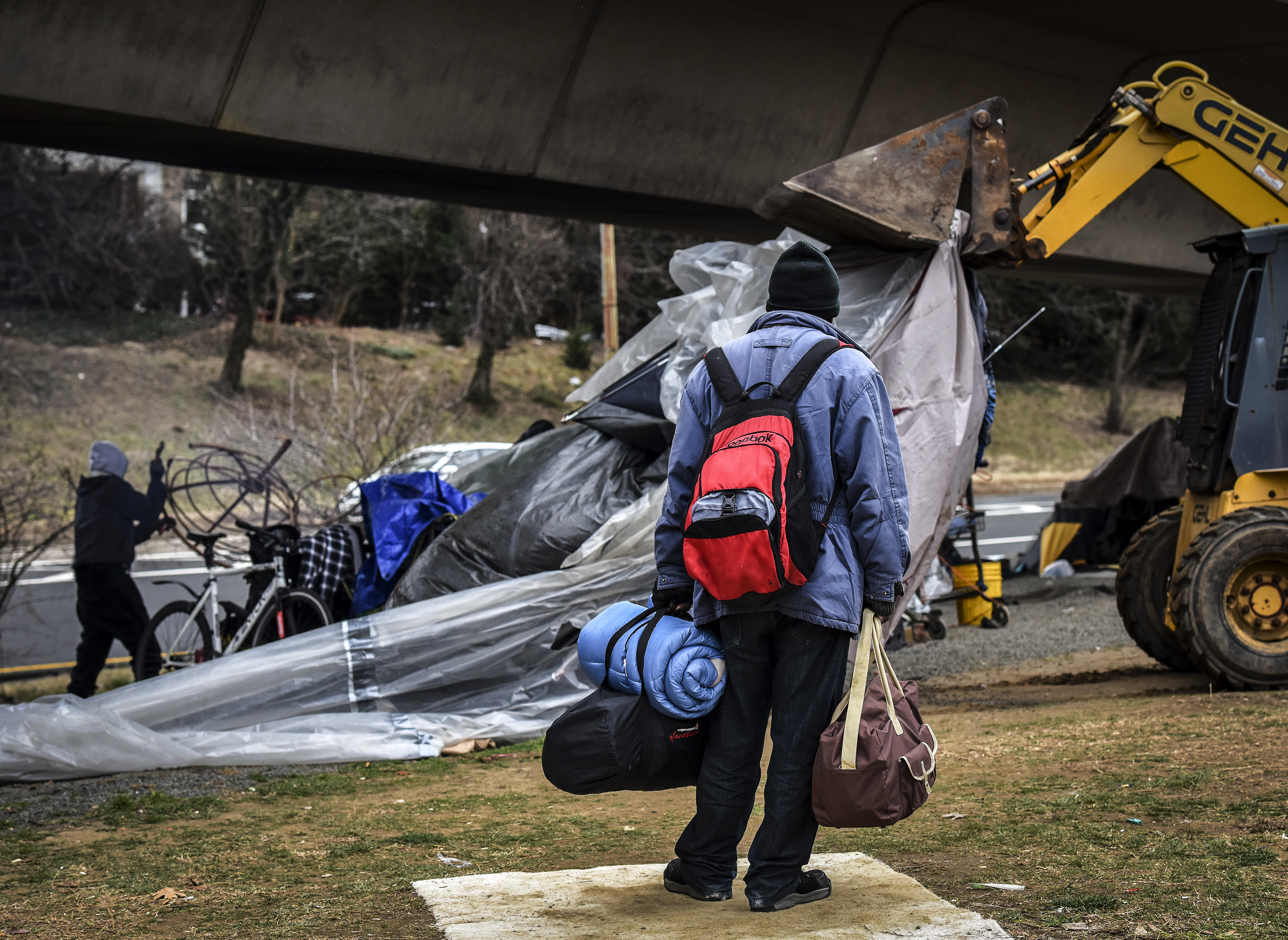 Authorities clear out a homeless tent encampment beneath the Whitehurst freeway, in Washington, DC.