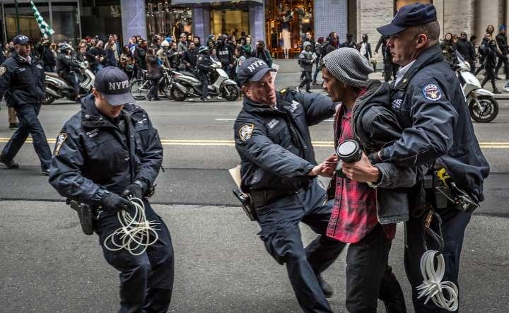Policemen Arrest a Protester atan Anti-Trump Rally.