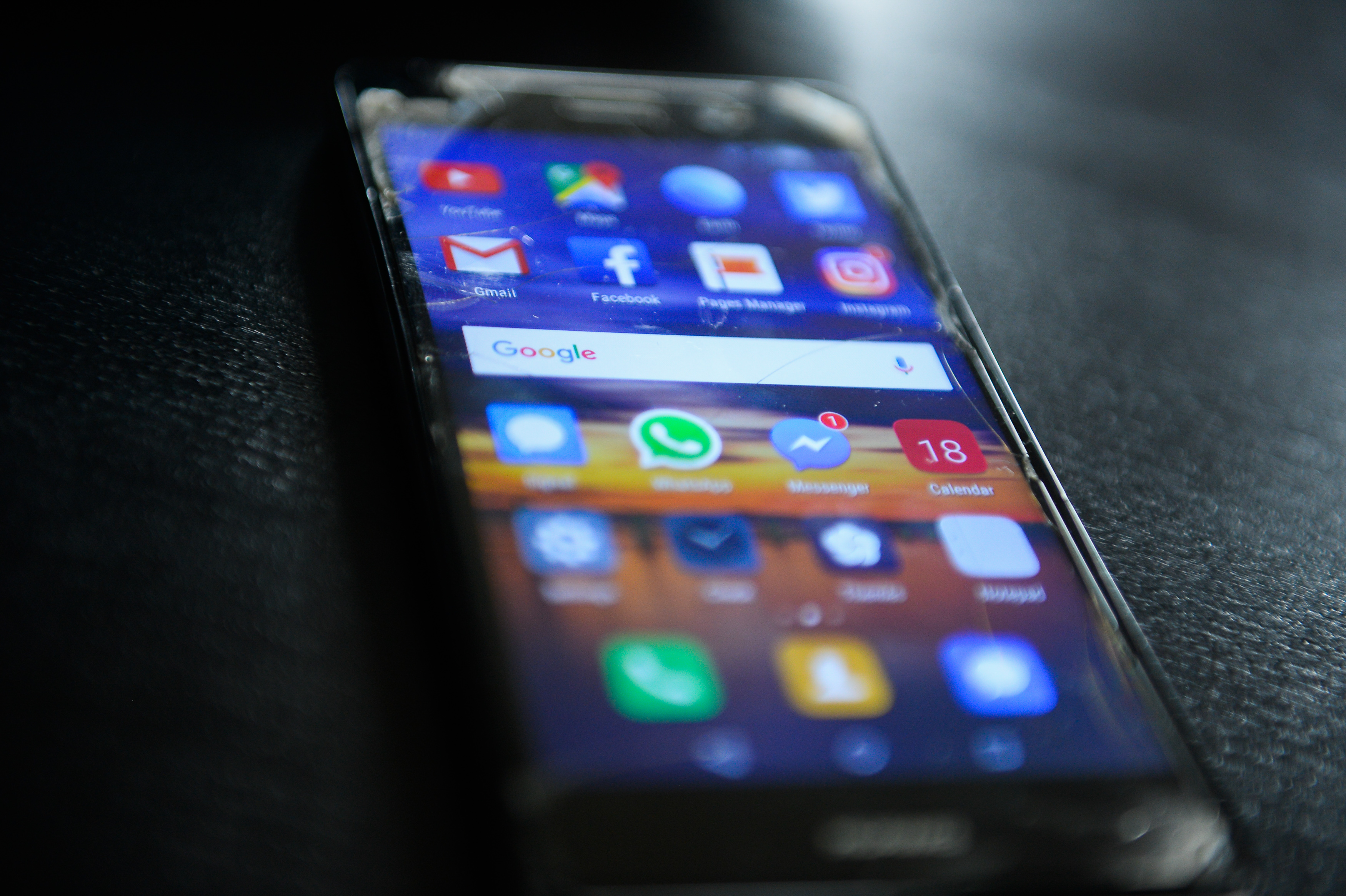 Social media icons are seen in a mobile device...