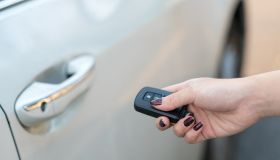 Car remote on hand, pressing button to unlock a car