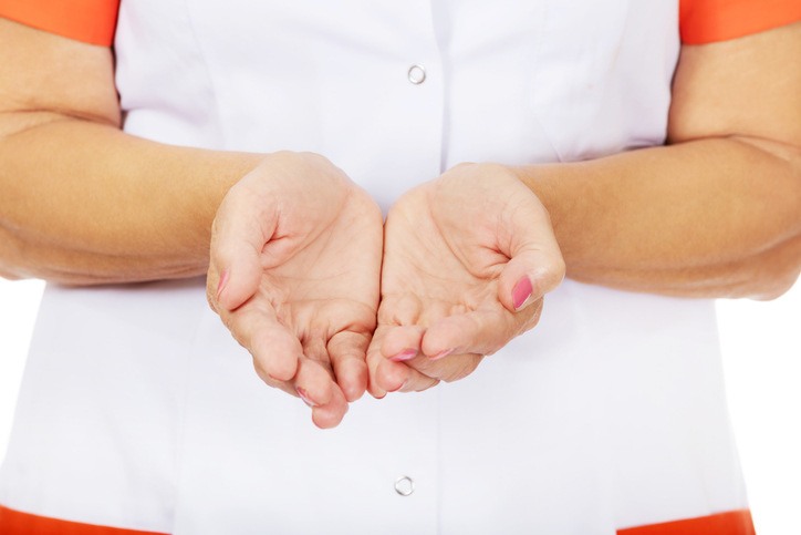 Midsection Of Nurse With Hands Cupped Over White Background