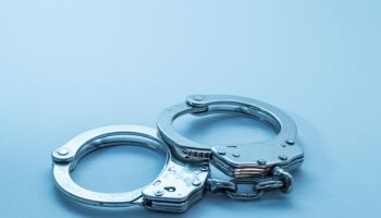 Close-Up Of Handcuffs Over Blue Background