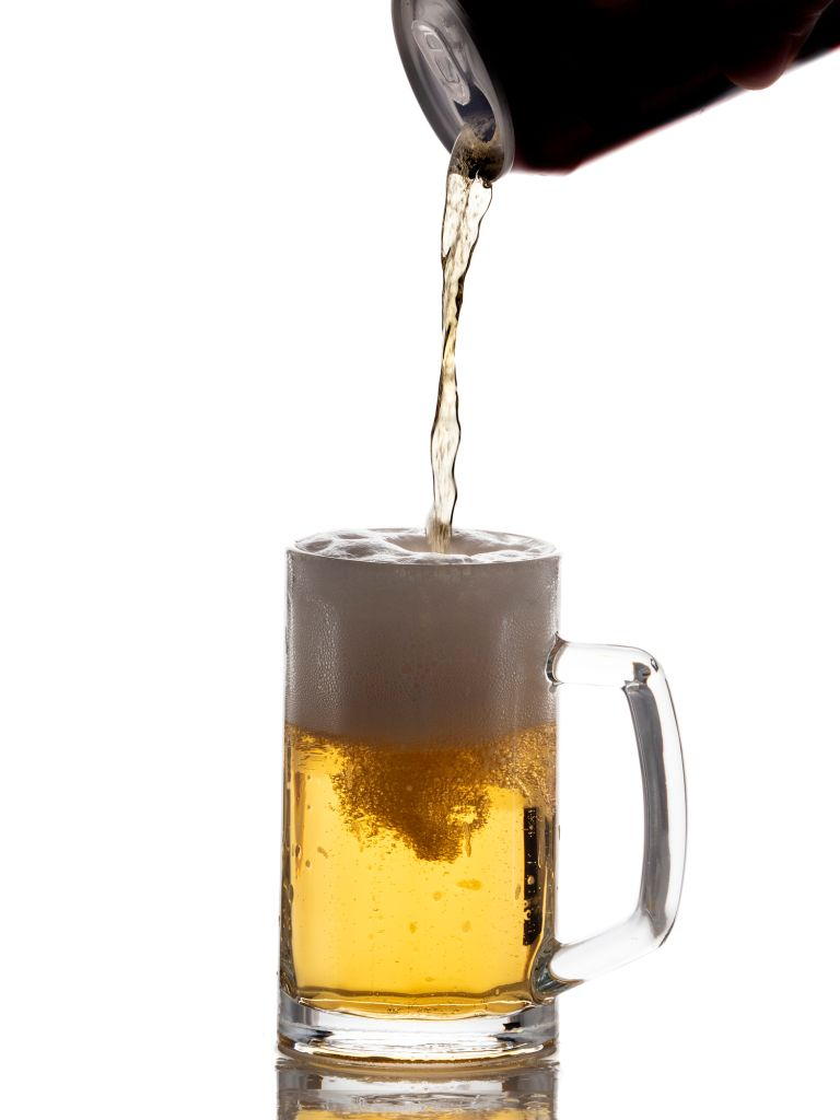 Aluminum drink can filling a glass of beer from on a white background.