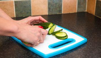 Woman's hands cutting fresh organic cucumber
