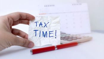 Tax time concept; hand is holding Tax Time written on the white paper note with a red pen and calendar.