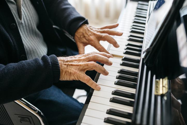 Crop view of senior man playing piano